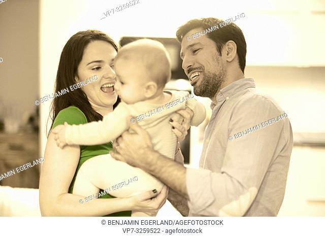 couple with baby in arm at home, in Munich, Germany
