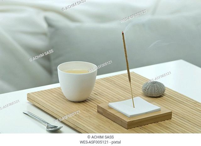 Aromatheraphy, tea, scent, aroma sticks, sea urchin shell, wellness, with a bed visible in the backgroud, studio