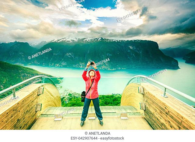 Tourism and travel. Woman tourist nature photographer taking photo with camera, enjoying Aurland fjord landscape from Stegastein lookout, Norway Scandinavia