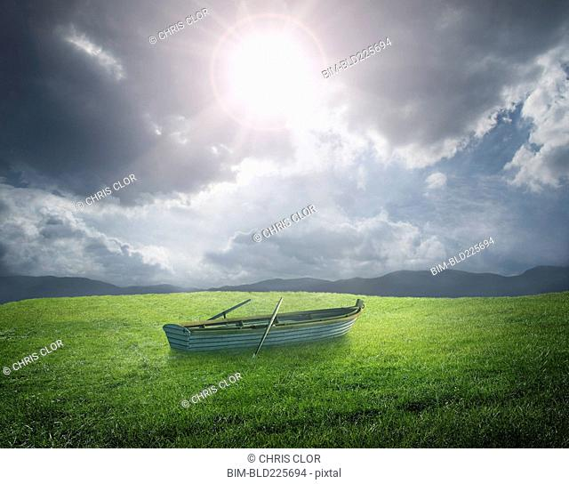 Abandoned rowboat in field of grass