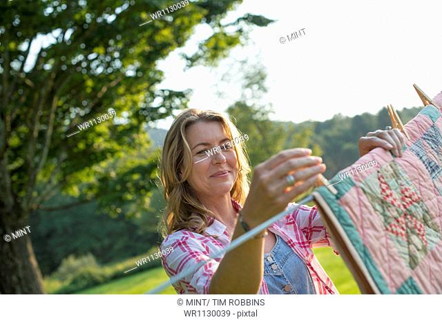 A woman hanging laundry on the washing line, in the fresh air