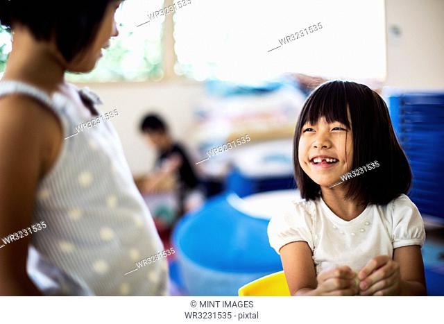 Two smiling girls in a classroom in a Japanese preschool
