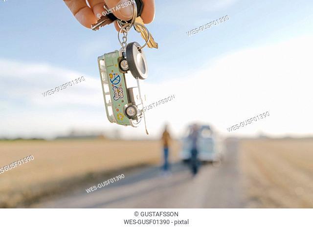 Hand holding camper van key in rural landscape