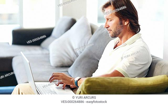 Mature couple on their couch looking at their laptop together, hugging and laughing