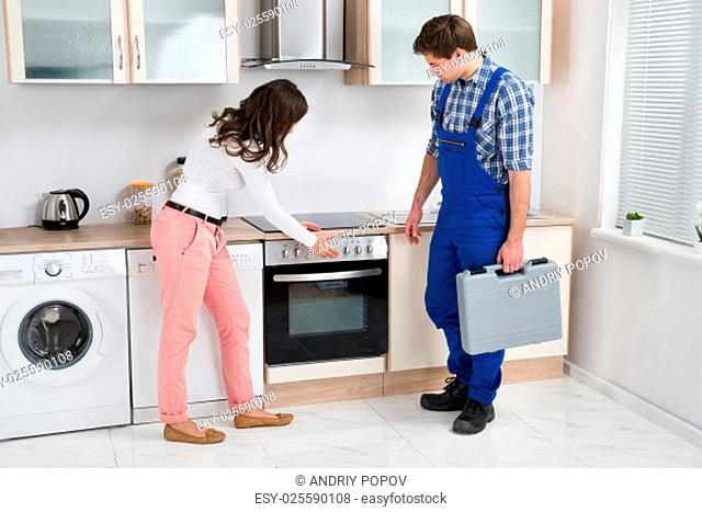 Young Housewife Showing Damaged Oven To Male Worker Holding Toolbox In Kitchen