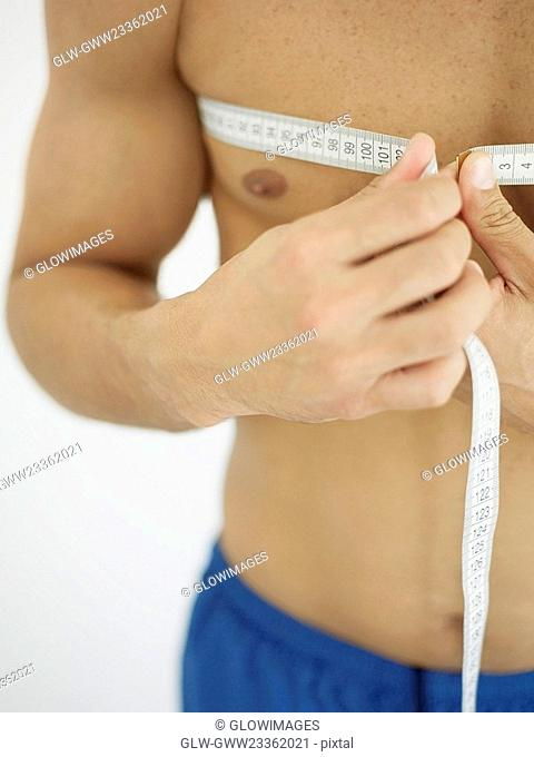 Mid section view of a person measuring his chest with a tape measure