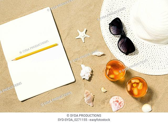 notebook, cocktails, hat and shades on beach sand