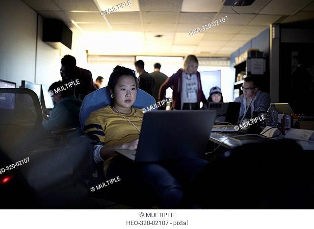 Focused young female hacker working hackathon at laptop in dark office