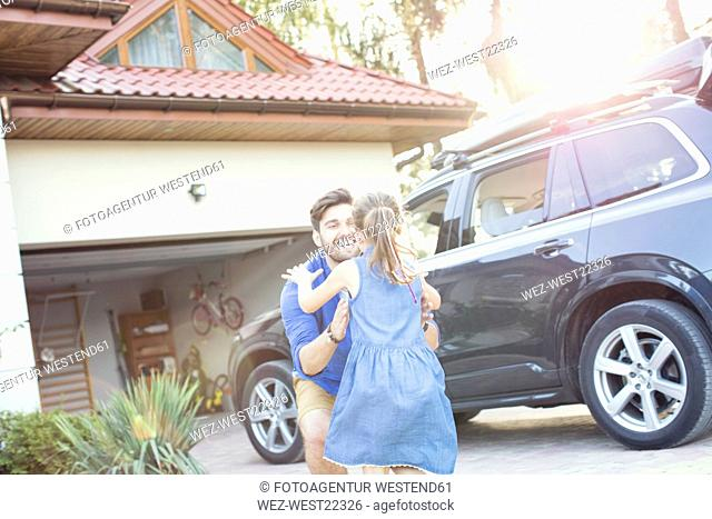 Father and daughter embracing in front of their car