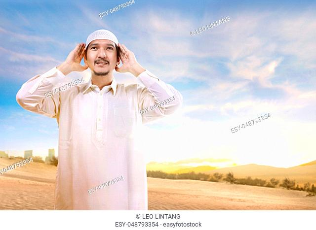 Smiling asian muslim man with cap standing and praying on the sand with blue sky background
