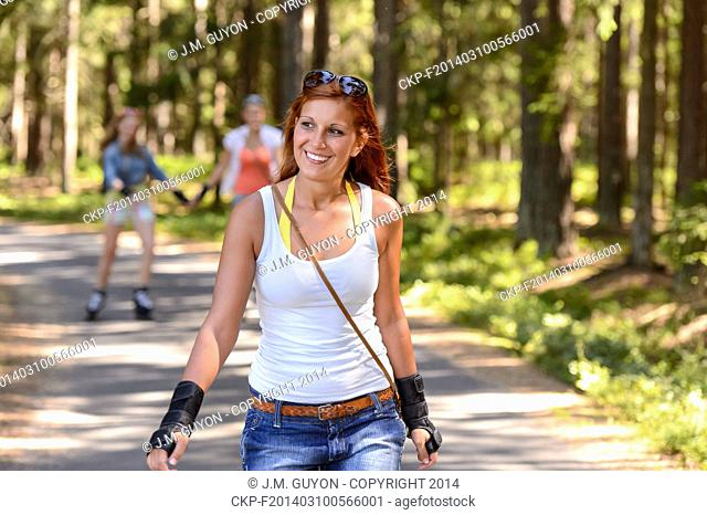Young woman roller skating outdoors summer sport on countryside road