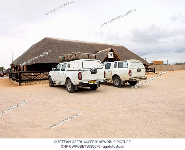 Namibia, Khomas, Solitaire, Two white cars parked in front of a building, stopover in Solitaire in front of the confectionery