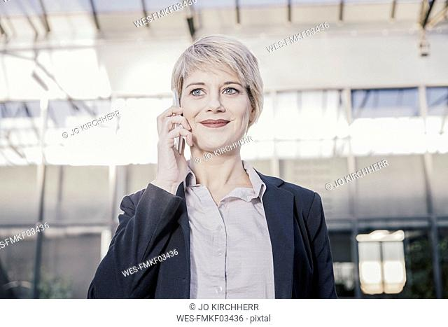 Portrait of smiling blond businesswoman on the phone