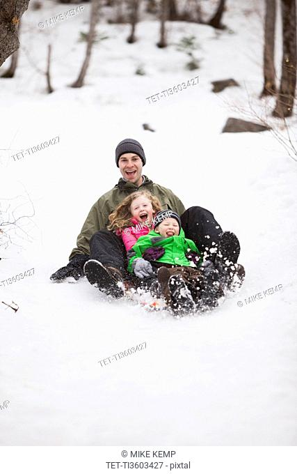 Portrait of young man sledding with children (4-5)