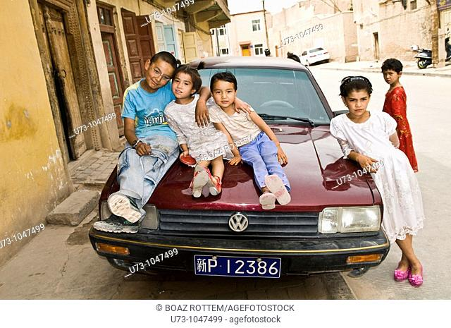 Children having fun while sitting on a Chinese Volkswagen car