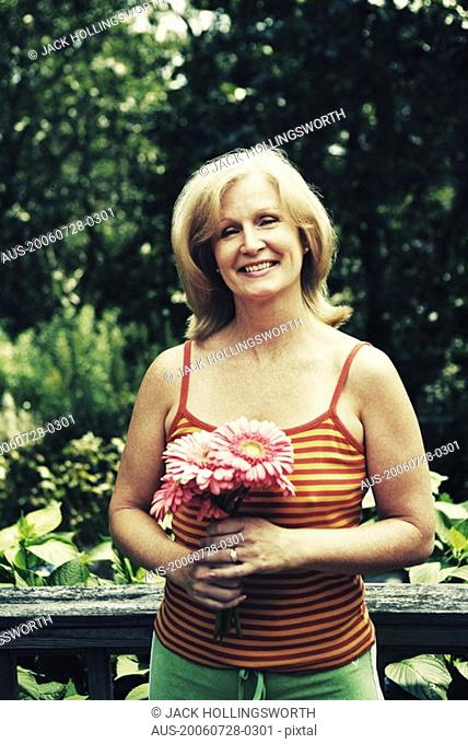 Portrait of a mature woman holding a bunch of flowers