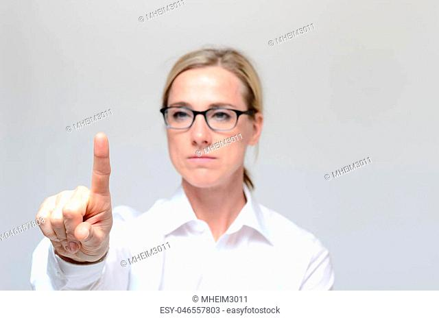 Businesswoman pressing a virtual button against grey background
