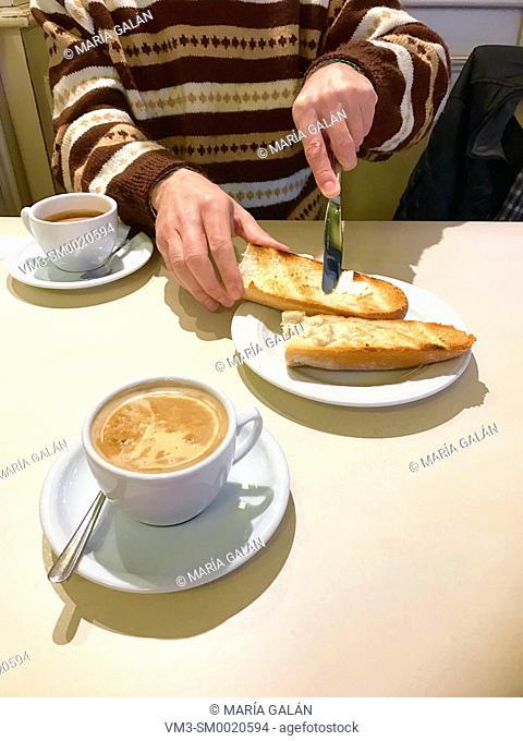 Man having breakfast, spreading butter on toast