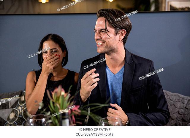 Couple at social gathering laughing