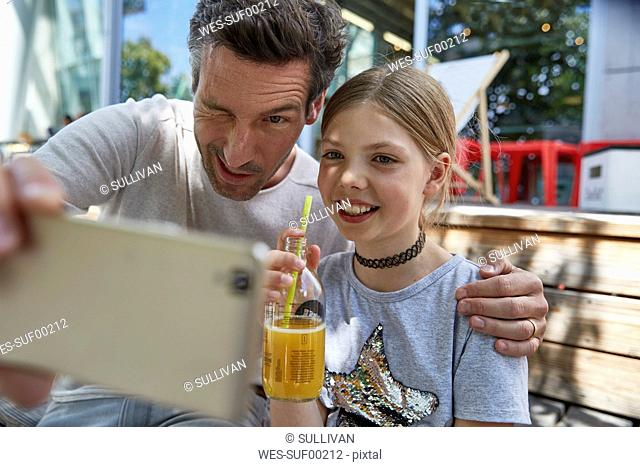 Playful father and daughter taking a selfie at an outdoor cafe