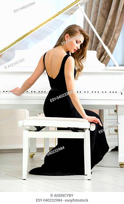Back view of woman in black dress sitting and playing piano. Concept of music and art