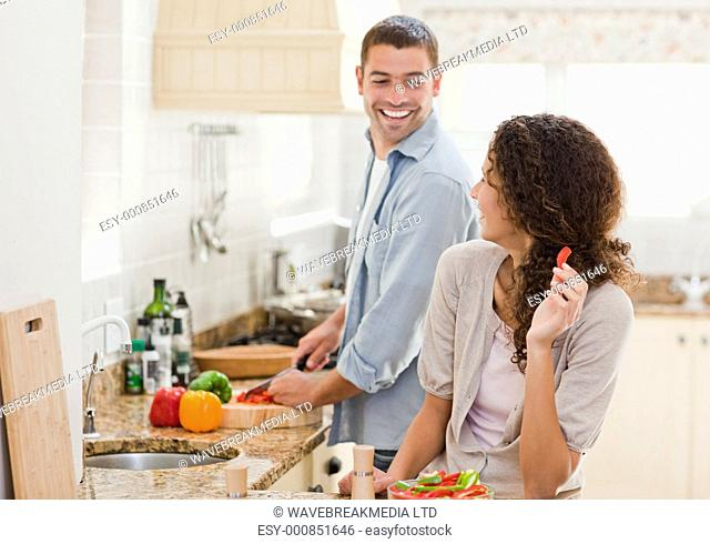 Beautiful woman looking at her husband who is cooking at home