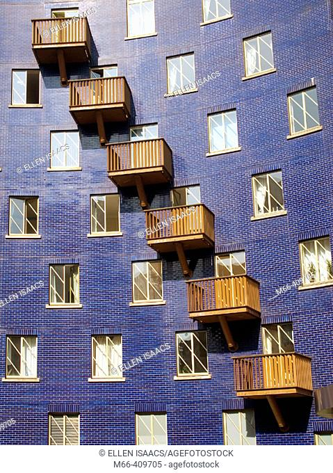 Pattern of windows and balconies on blue brick building in warehouse district of London, England