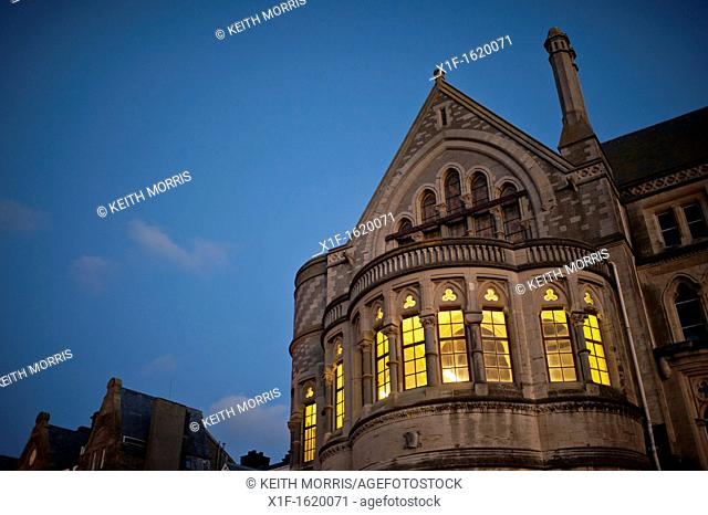 Lights shining through the windows of Aberystwyth University 'Old College' at night, exterior, Wales UK