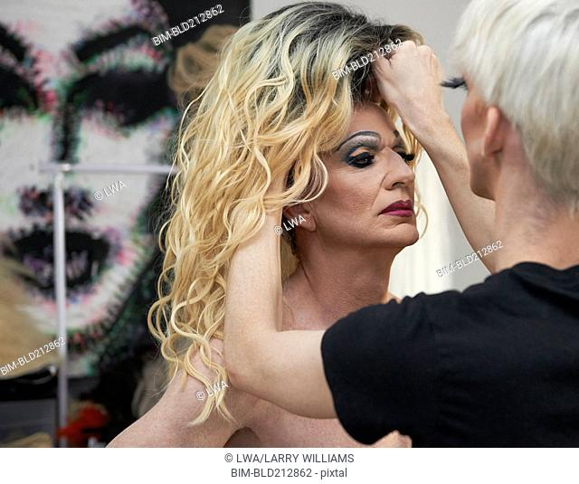 Caucasian drag queen fixing colleague's wig in bathroom