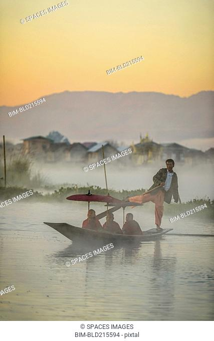 Asian gondolier rowing monks in canoe on river