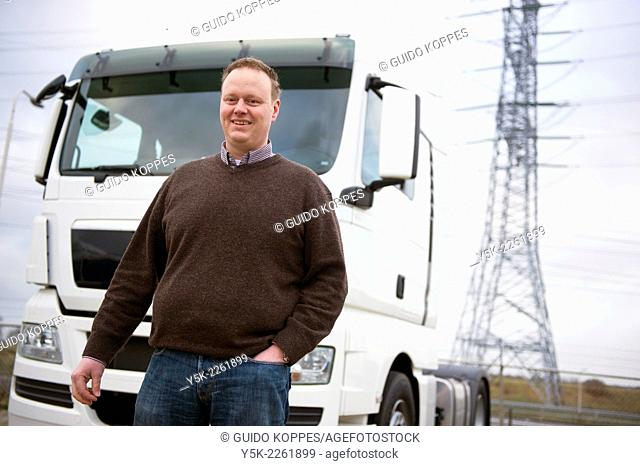 Tilburg, Netherlands. Manager at a truck overhall and maintenance company in front of a truck of one of his customers