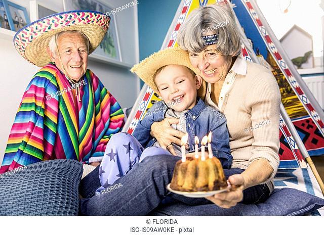 Senior couple and grandson celebrating with birthday cake on living room floor