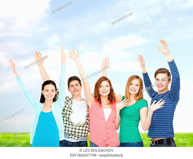 education and people concept - group of smiling students standing and waving hands