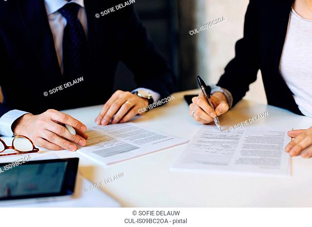 Businessman and woman in meeting, signing documents, mid section