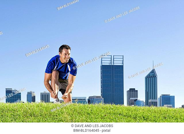 Caucasian runner tying shoes on grassy hill near Perth city skyline, Western Australia, Australia