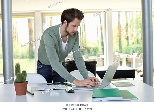 Man working on a laptop with a cactus plant on the table