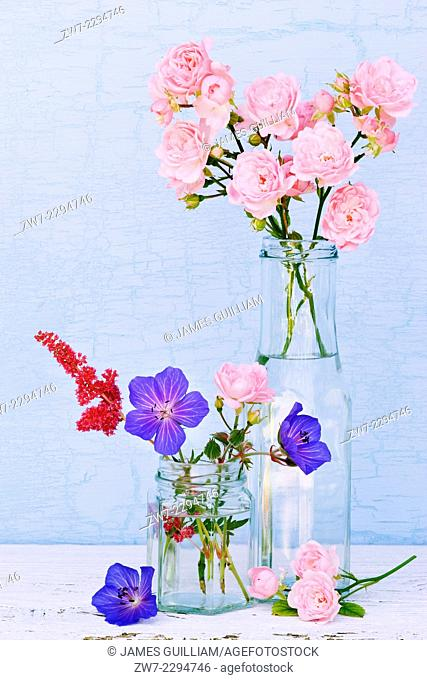 Glass containers filled with Geranium, Astilbi and miniture Rose flowers
