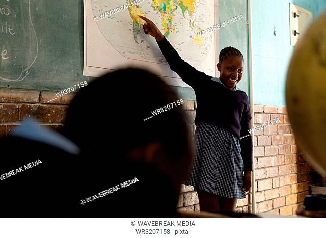 Schoolgirl explaining about world map in classroom