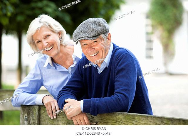 Couple smiling by wooden fence