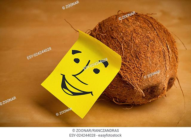Post-it note with smiley face sticked on a coconut