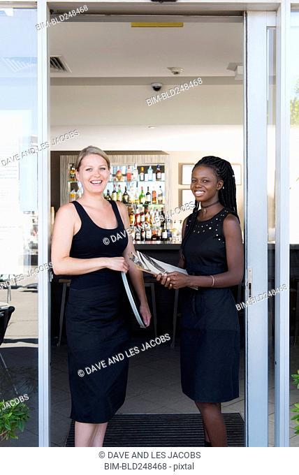 Smiling hostesses standing in doorway