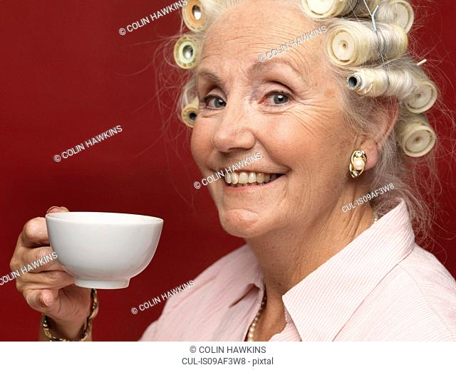 Studio portrait of senior woman in hair rollers with cup of tea