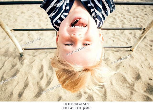 Portrait of boy hanging upside down over sand, smiling, Santa Barbara, California, USA