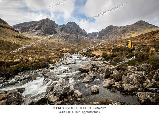 Hiker next to a river with the Black Cuillin's Bla Bheinn Mountain, Isle of Skye, Scotland