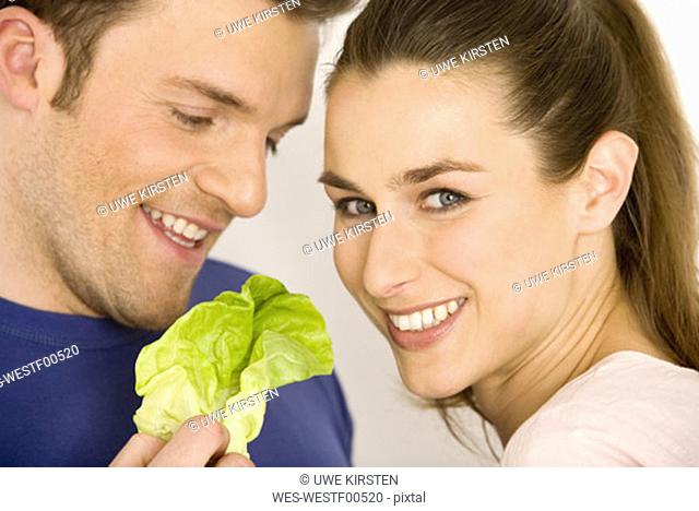Young couple with lettuce leaf, smiling, close-up