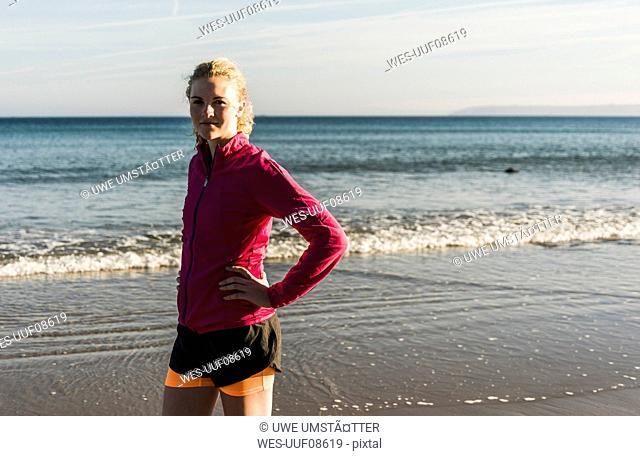 France, Crozon peninsula, sportive teenage girl standing on the beach