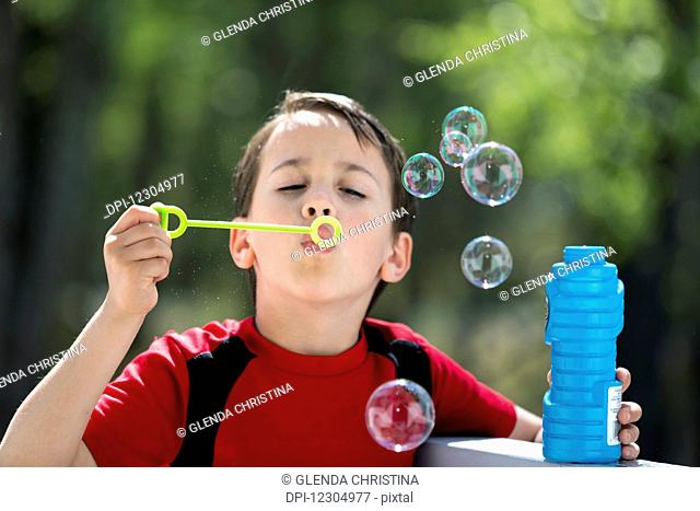 Boy playing with and blowing bubbles in summer, Palmer, Southcentral Alaska