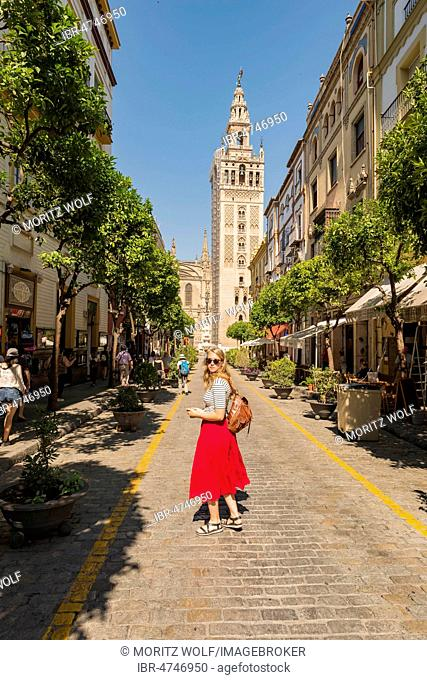 Woman with red dress on street, behind La Giralda, belfry of Seville Cathedral, Catedral de Santa Maria de la Sede, Seville, Andalusia, Spain