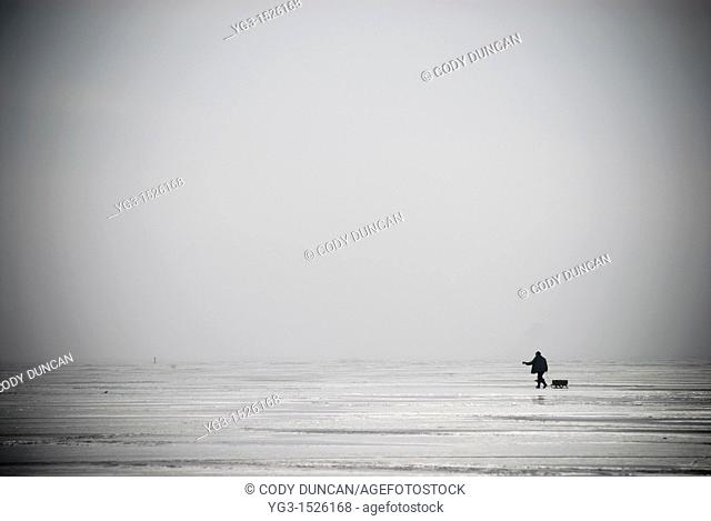 Lone Ice fisherman walking across a frozen Curonian Lagoon, Lithuania
