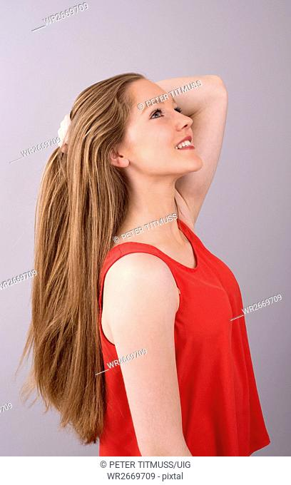 Portrait of a teenage girl with hands in her long hair